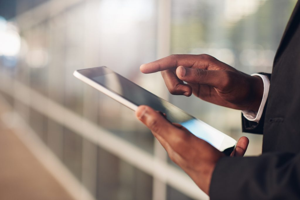 Cropped closeup of the hands of a businessman of African descent holding and using a digital tablet, wiht blurred office windows in the background
