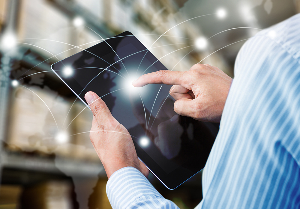 man holding tablet with overlaid conceptual illustration of shipping routes