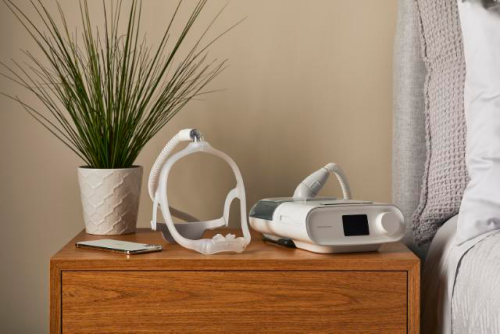 CPAP and mask sitting on nightstand next to a decorative plant
